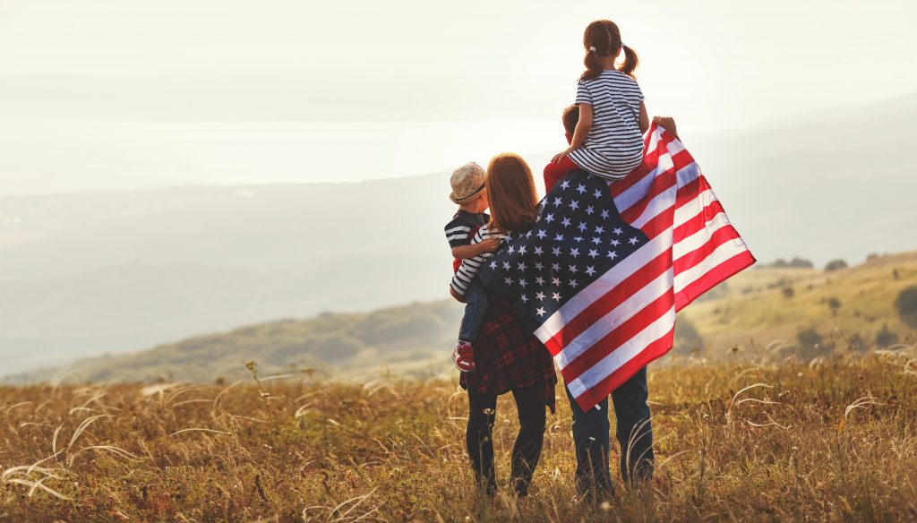 Happy Family With Flag Of America Usa At Sunset Outdoors